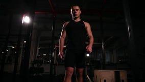 健身房的一个人跳与一跳的桦树在一个木立方体,然后立刻进行举酒吧到二头肌 股票录像