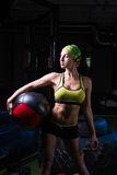 健身房的一个坚强的女孩训练与球 健康,体育概念 免版税库存照片
