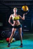 健身房的一个坚强的女孩训练与球 健康,体育概念 免版税库存图片