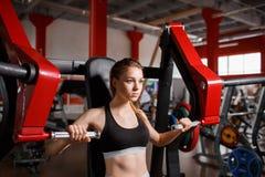 健身房的一个女孩在发嗡嗡声的东西模拟器 库存照片