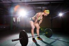 健身房的一个美丽的女孩训练腿的肌肉,并且后面, deaet锻炼deadlift,坐与重量,拿着酒吧我 免版税图库摄影