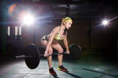 健身房的一个美丽的女孩训练腿的肌肉,并且后面, deaet锻炼deadlift,坐与重量,拿着酒吧我 图库摄影