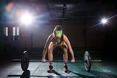 健身房的一个美丽的女孩训练腿的肌肉,并且后面, deaet锻炼deadlift,坐与重量,拿着酒吧我 库存照片