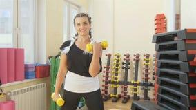 健身房的一名妇女训练她的胳膊肌肉反对运动适应背景妇女的的体育夫人 影视素材