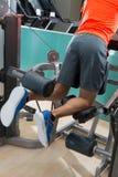 健身房的下跪的腿大腿骨卷毛人 库存照片
