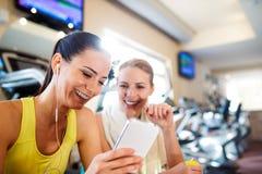 健身房的两名可爱的适合妇女与巧妙的电话 免版税库存图片