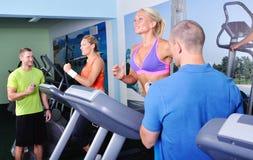 健身房的两名妇女行使与个人健身教练员的 免版税库存照片