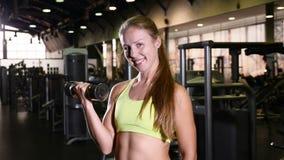 健身房的举行哑铃微笑对照相机的运动妇女画象  概念健康生活 美丽的年轻人 4K 影视素材