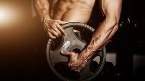 健身房的人 做与杠铃的肌肉爱好健美者人锻炼 坚强的人用有静脉的紧张的强的男性手 库存照片
