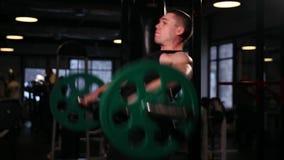 健身房的体育运动员提高与重量的标准在他的从坐姿的头上 特写镜头照相机移动 股票录像