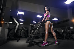健身房的健身女孩在体育穿戴 免版税库存图片