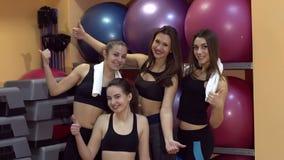 健身房的四个体育女孩显示他们的赞许 股票录像