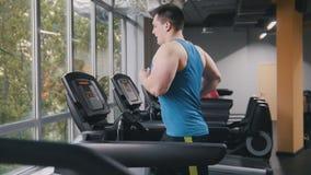 健身房的大力士-跑在健身房的连续轨道的爱好健美者 免版税库存图片