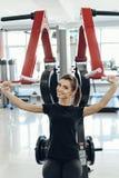 健身房的女孩在模拟器 免版税库存图片
