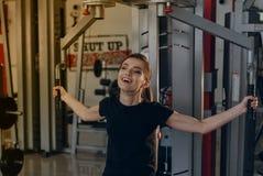 健身房的女孩在模拟器 免版税库存照片