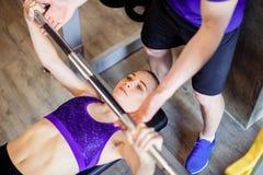 健身房的妇女与行使与杠铃的个人健身教练员力量体操 库存照片