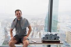 健身房的年轻人在锻炼以后,坐在俯视现代城市摩天大楼的宽窗口前面的一条长凳 库存照片