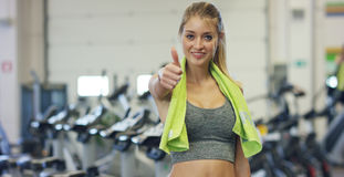 健身房的微笑与在放松她的肩膀的一块毛巾的年轻美丽的女孩,立场在教练以后和 概念:对爱spor 库存照片