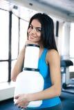 健身房的微笑的妇女与体育营养 库存照片