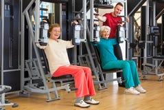 健身房的微笑的年长妇女与辅导员 库存图片