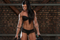 健身房的性感的妇女用锻炼设备 图库摄影