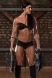 健身房的性感的妇女用锻炼设备 库存图片