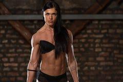 健身房的性感的妇女用锻炼设备 免版税库存照片
