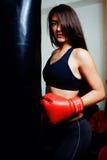 健身房的性感的战斗机女孩与拳击袋子 免版税库存图片