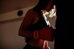 健身房的性感的战斗机女孩与拳击袋子 图库摄影