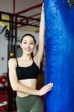健身房的战斗机女孩与拳击袋子 长的头发妇女健身ufc模型 免版税库存照片
