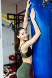 健身房的战斗机女孩与拳击袋子 长的头发妇女健身ufc模型 免版税库存图片