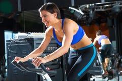 健身房的有氧运动转动的显示器教练员妇女 免版税库存图片