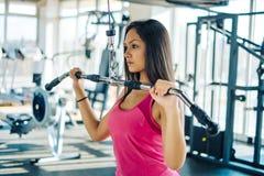健身房的美丽的年轻健身女孩 做三头肌锻炼 库存照片