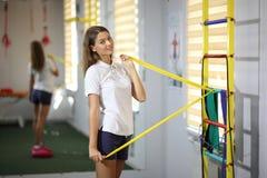 健身房的美丽,性感的女孩 一个美丽的女孩参与与扩展器的健身 库存照片