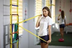 健身房的美丽,性感的女孩 一个美丽的女孩参与与扩展器的健身 免版税图库摄影