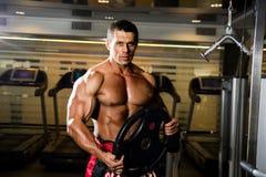 健身房的英俊的肌肉人 有圆盘的举重运动员 免版税库存照片