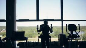 健身房的行使在xtrainer机器的可爱的少妇剪影  股票录像