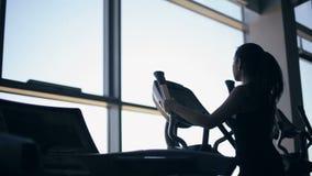 健身房的行使在xtrainer机器的可爱的少妇剪影  影视素材