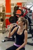 健身房的金发碧眼的女人用水 免版税图库摄影