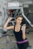 健身房的金发碧眼的女人用水 免版税库存图片