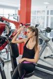 健身房的金发碧眼的女人用水 库存照片