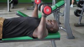 健身房的非洲人做哑铃躺下的卧推锻炼  股票视频