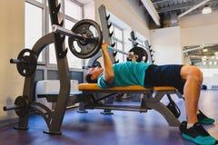 健身房的年轻人行使在卧推的胸口与杠铃 免版税库存照片