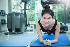 健身房解决crossfit的妇女做俯卧撑 库存图片