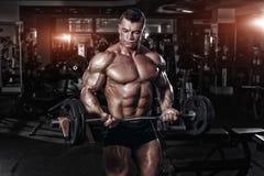 健身房训练的运动员肌肉爱好健美者与酒吧 免版税图库摄影