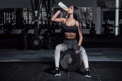 健身教练员喝从瓶的水 免版税库存图片