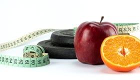 健身概念、哑铃用红色苹果,半桔子和测量的磁带 免版税库存照片