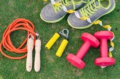 健身概念用在绿草backgroun的锻炼设备 图库摄影
