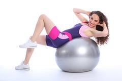 健身由健康微笑的妇女的球执行 免版税库存照片