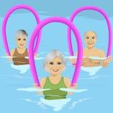 健身的资深人把做与泡沫路辗的水色有氧运动分类在游泳池有空的中心 免版税图库摄影